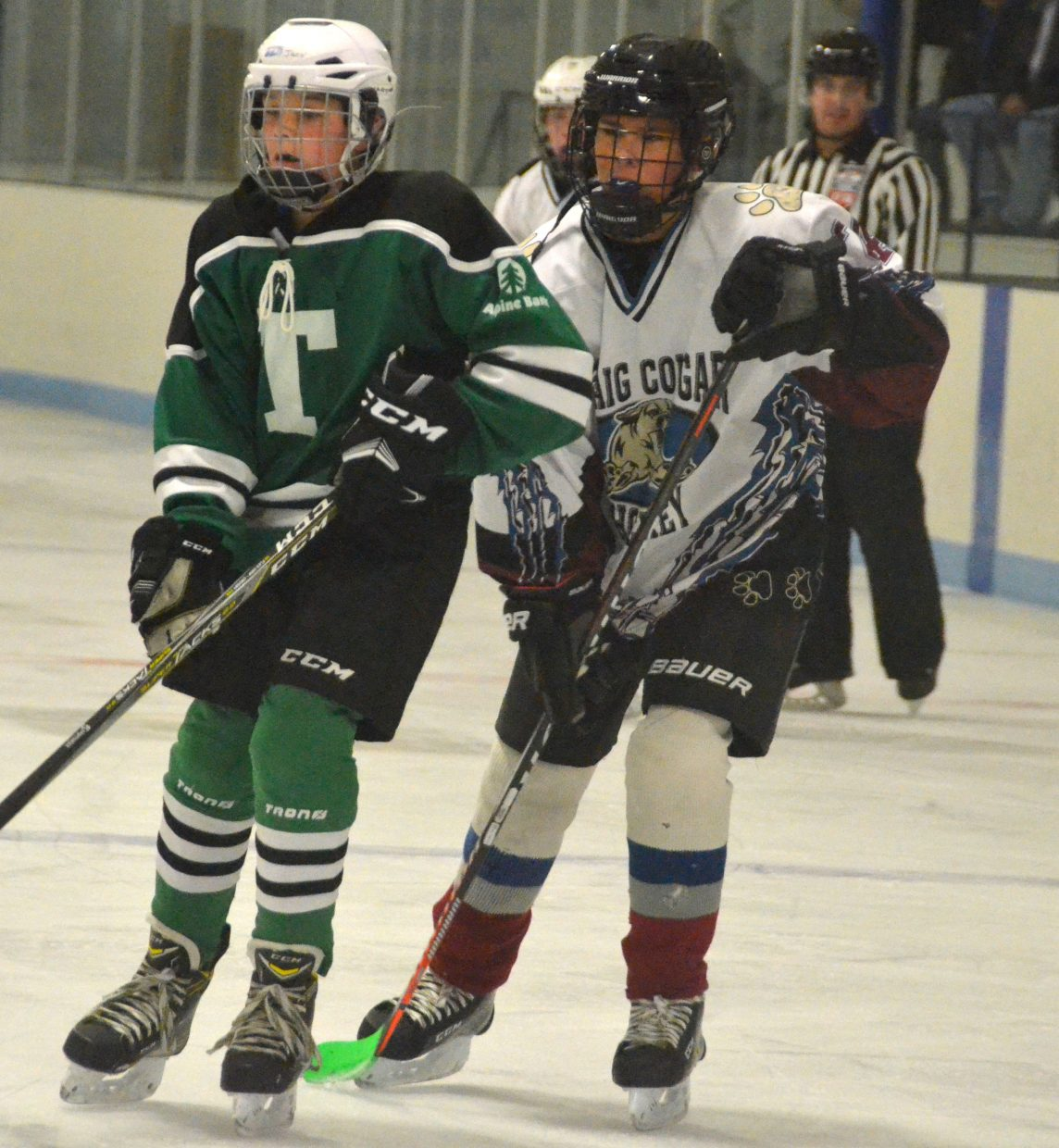 Forrest Siminoe stays close with his opponent during Craig Youth Hockey Association's 14U Bantam game against Telluride.