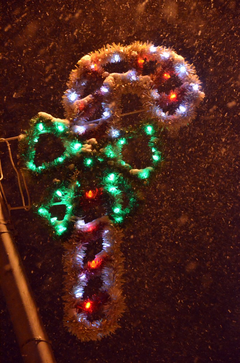 Snow swirls around a candy cane decoration above Victory Way during downtown Craig's Parade of Lights Saturday night.