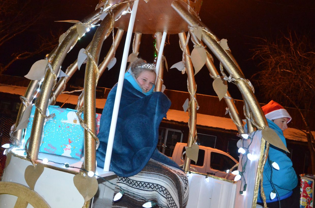 Moffat County High School's Caroline Riley stays bundled up in Cinderella's carriage on MCHS theater's float as part of downtown Craig's Parade of Lights Saturday night.