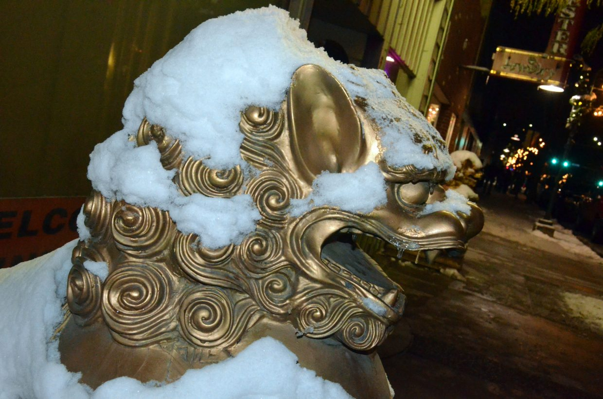 The golden lions outside Spicy Basil are coated with snow Saturday evening.
