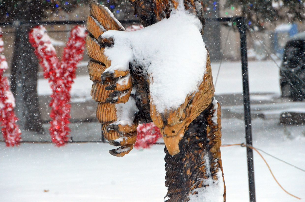 The wooden eagle sculpture outside Craig City Hall is grounded due to heavy snow Saturday afternoon.