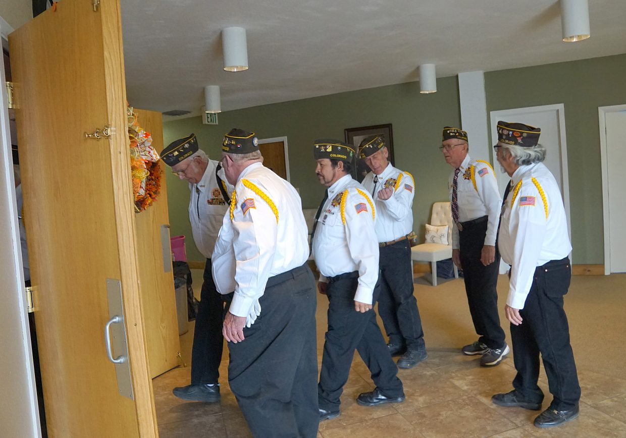 Members of the Veterans of Foreign Wars Craig Post 4265 color guard re-enter the Lighthouse of Craig sanctuary after their salute to the flag.