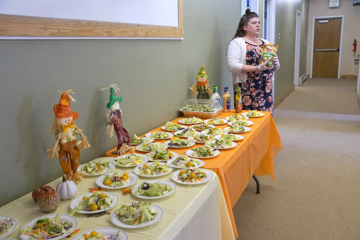 Lighthouse of Craig partitioner Aubree Webb stands ready to help with salad — part of a Thanksgiving day dinner to honor veterans.
