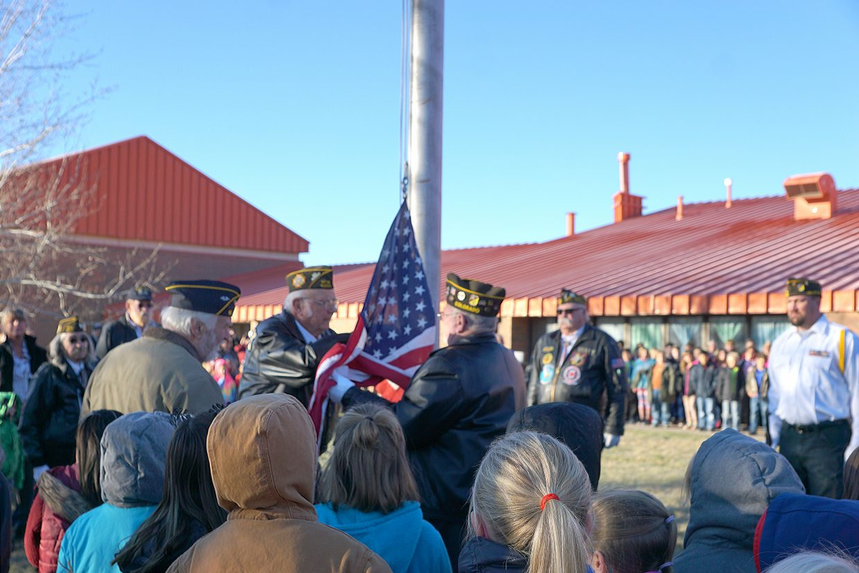 School children watch as the VFW Color Guard prepares to raise the American flag.