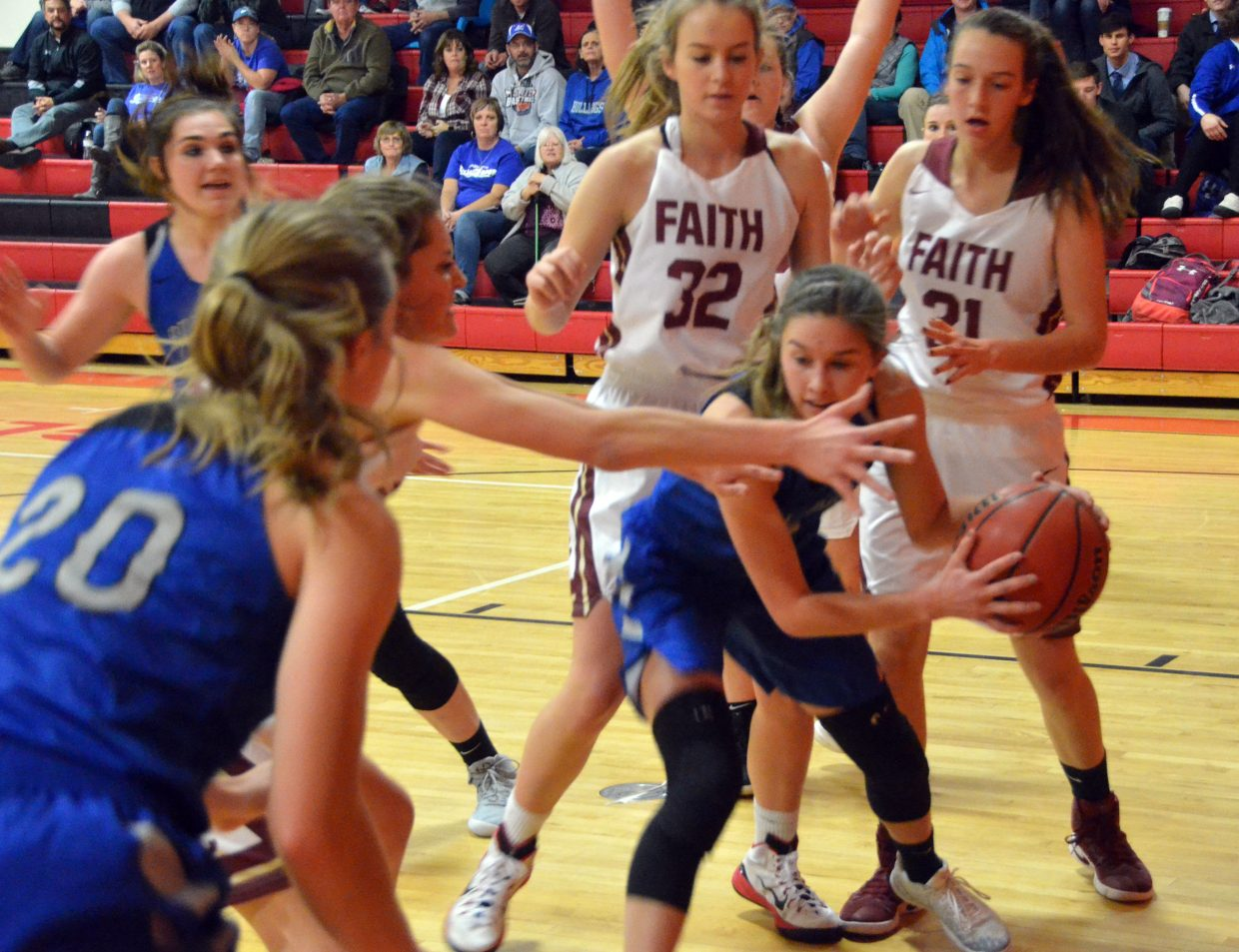 Moffat County High School's Emaleigh Papierski looks to pass from down low Faith Christian.