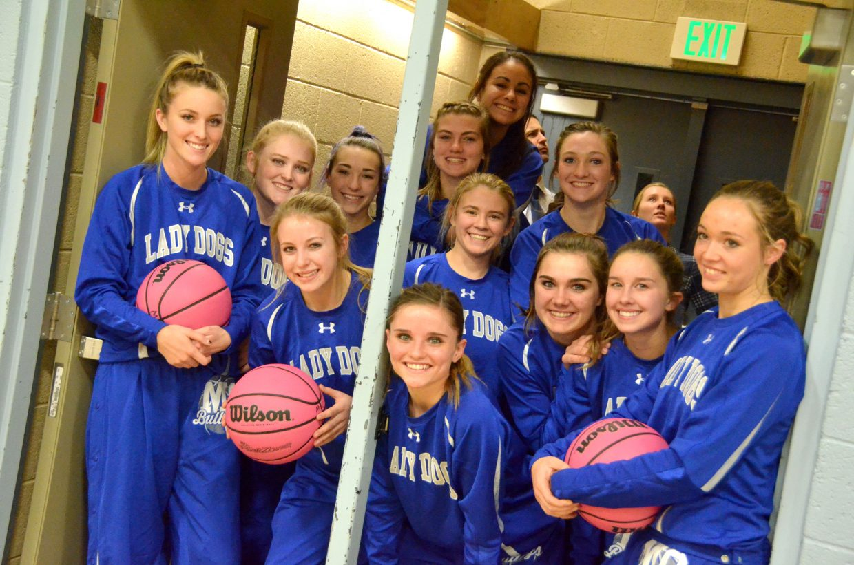 The Moffat County High School girls varsity basketball team prepares for the big entrance during Wednesday's games against Steamboat Springs.