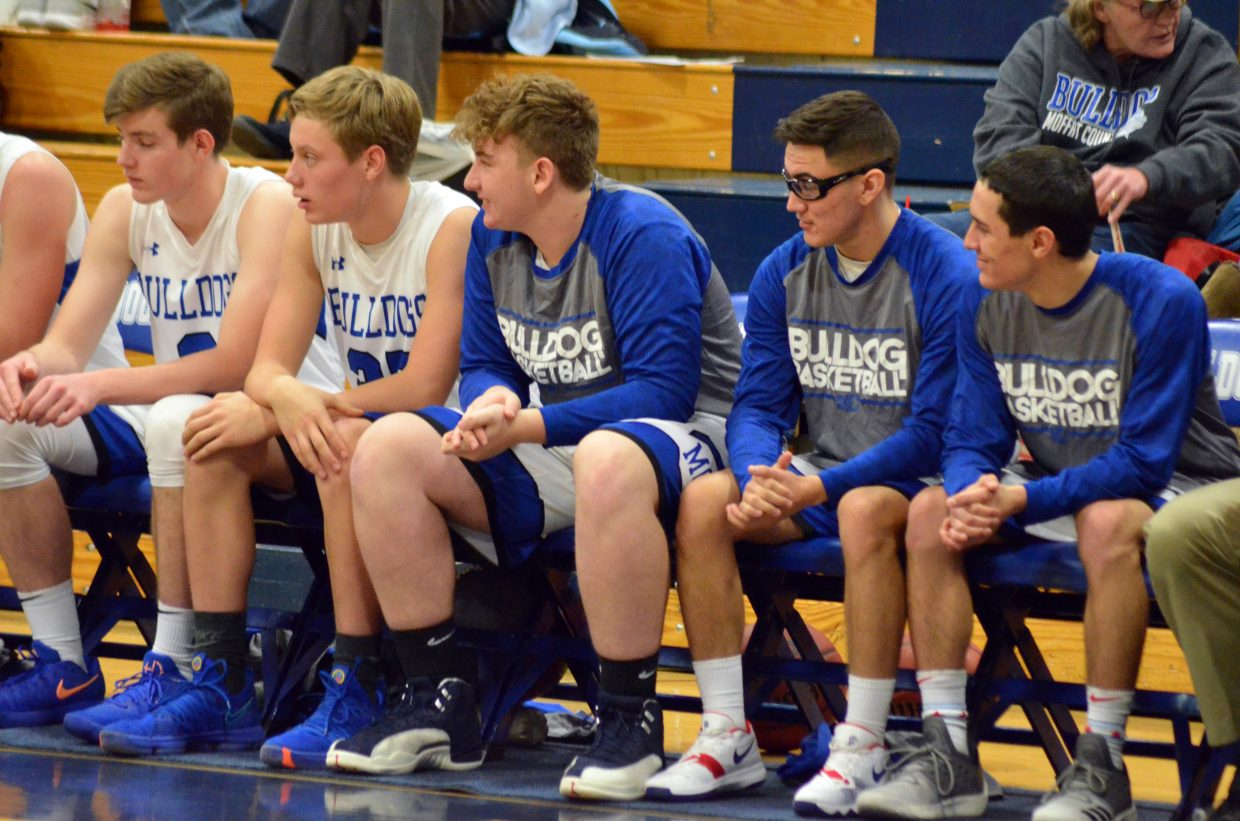 The Moffat County High School boys basketball bench observes the action against Steamboat Springs.