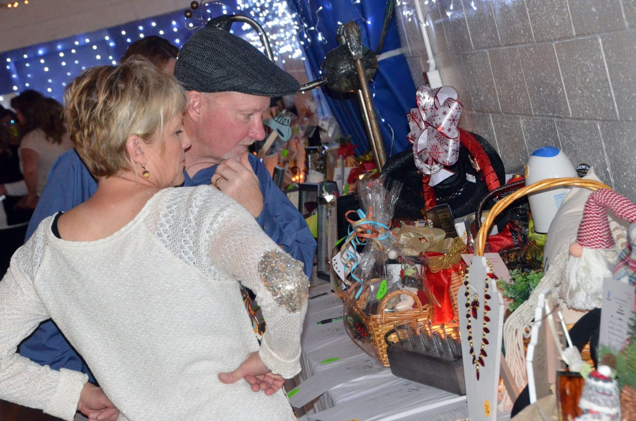 Spectators look over silent auction items during Cowboy Christmas at Boys & Girls Club.
