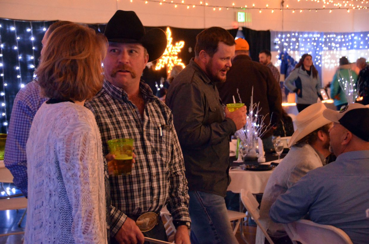 Audience members contemplate auction bids during Cowboy Christmas at Boys & Girls Club.