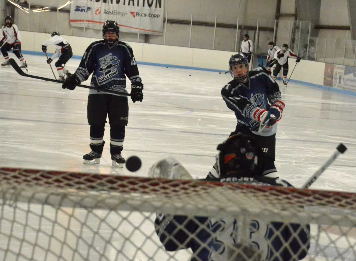 Garett Stockman unleashes a slapshot during warmups between games for Moffat County Bulldog hockey.