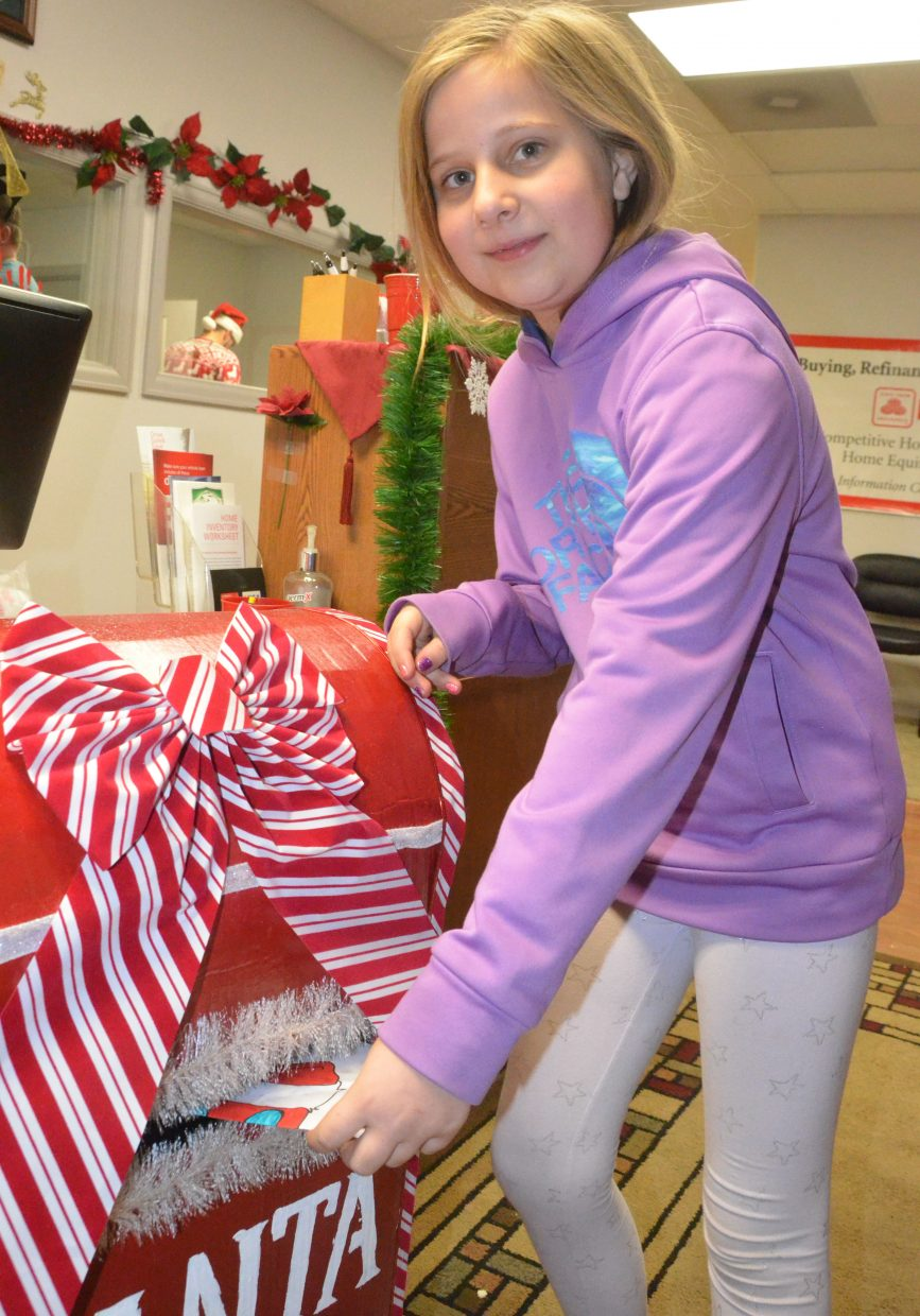 Rye Ocker drops off her letter to Santa in the specialty mailbox.