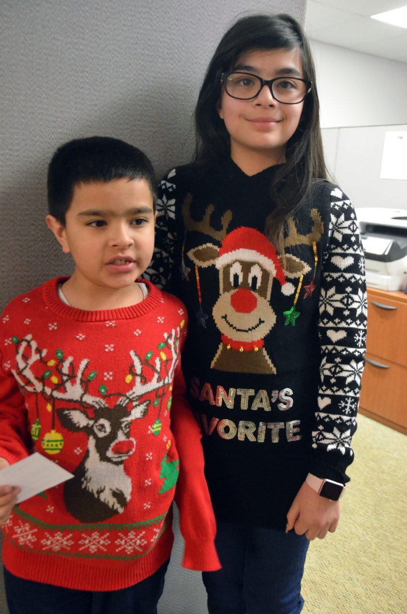 Diego, 8, and Yoselin Guevara, 11, display their holiday sweaters during Letters to Santa.