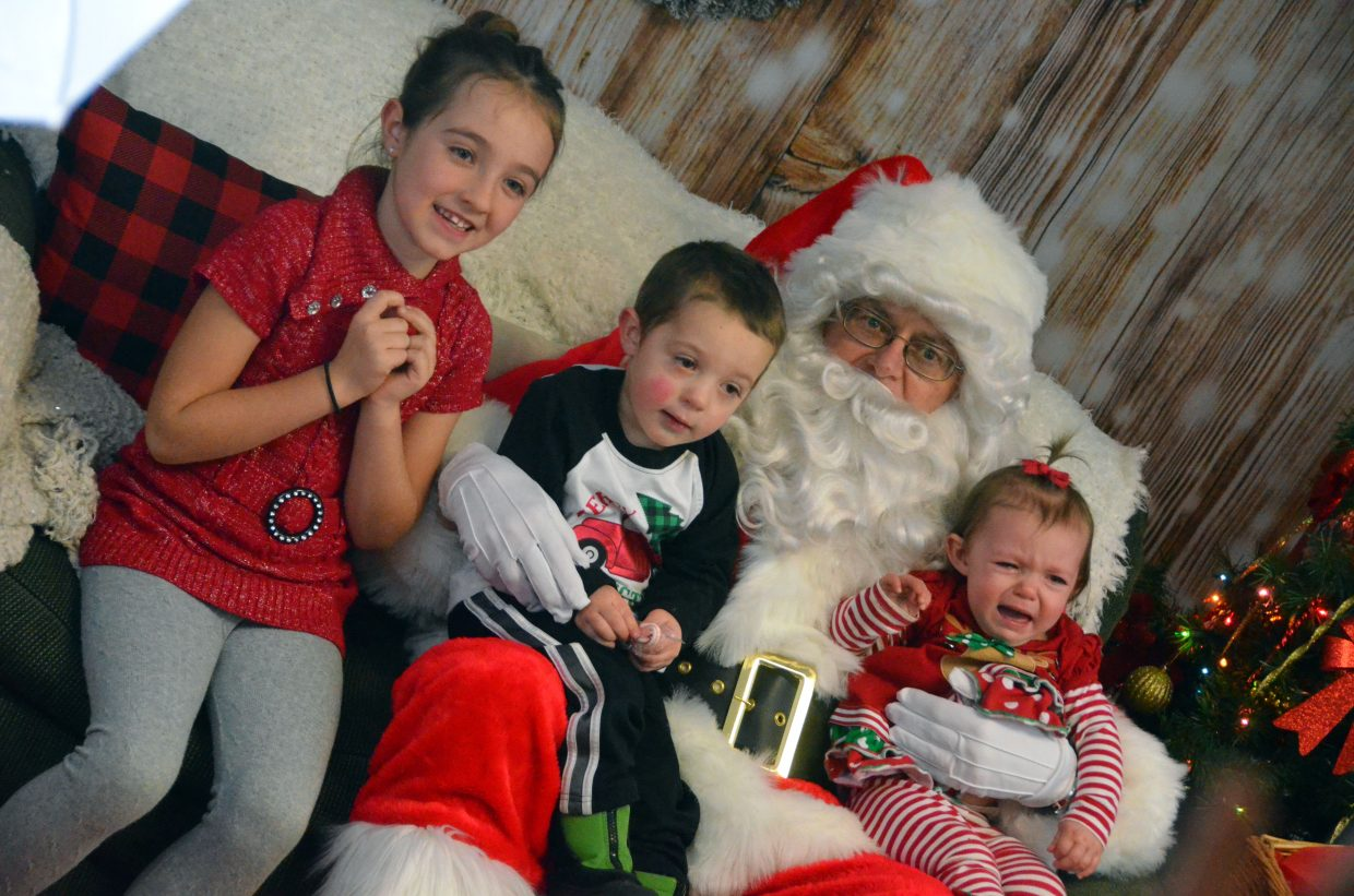 Siblings Kaylee, 7, Cameron, 2, and Holly, 1, have different reactions to meeting Santa Claus.