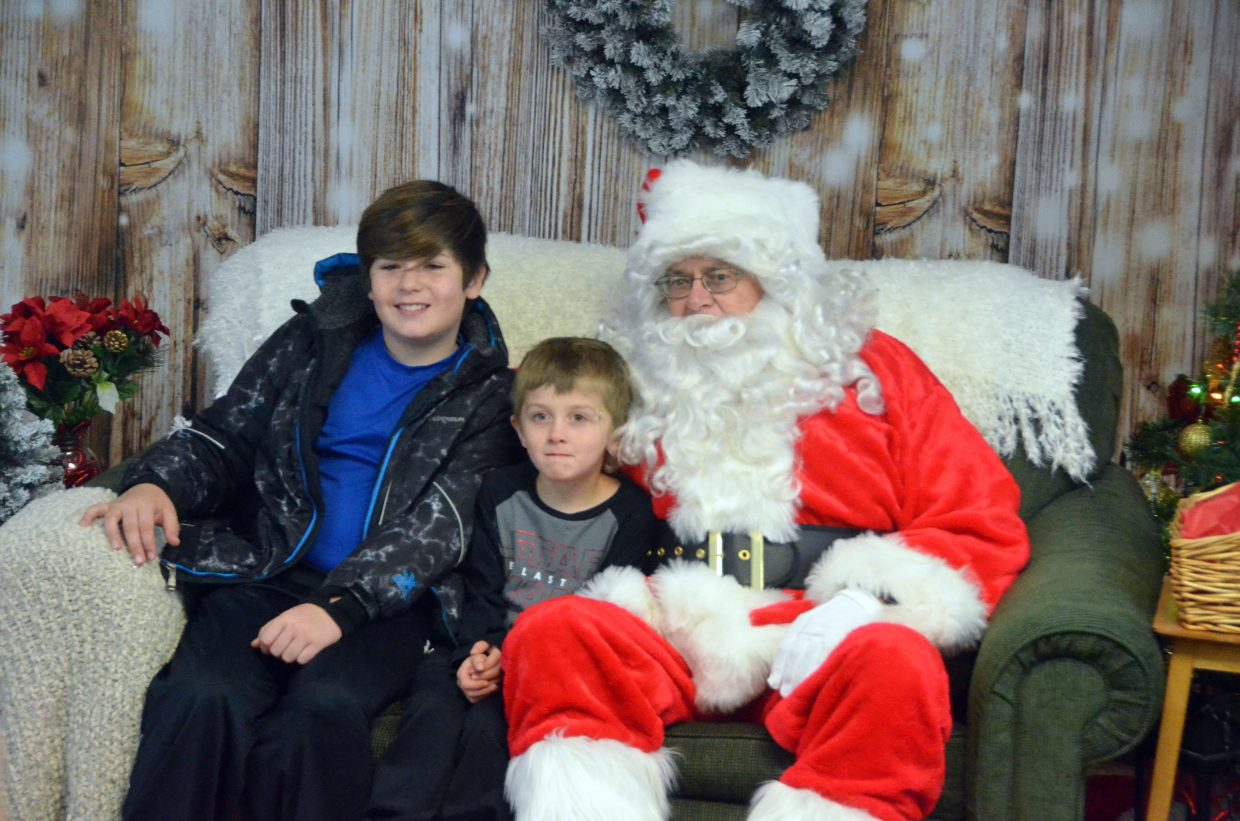 Myca, 11, and Josiah Marshall, 5, grin for the camera with Santa.