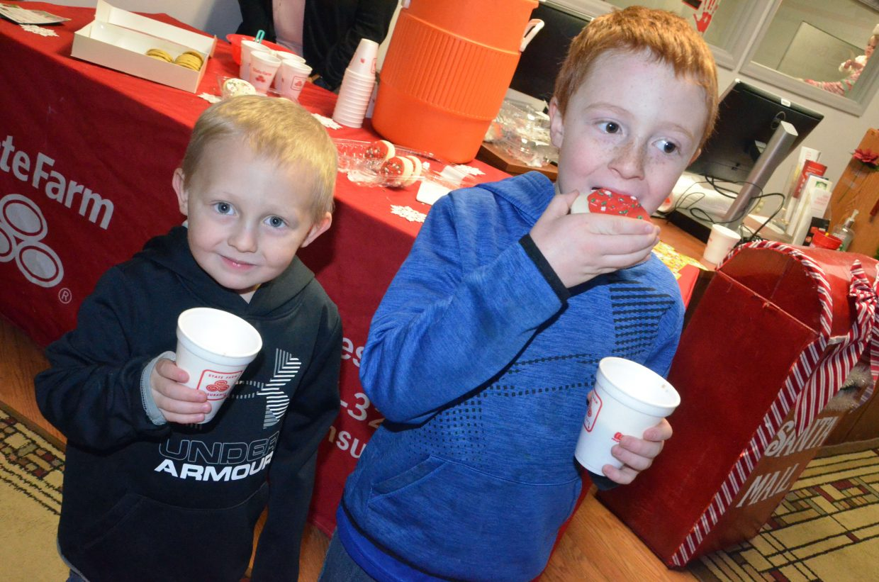 Brothers Ryker, 3, and Thane Nielson, 7, chow down on cookies and cocoa during Letters to Santa.