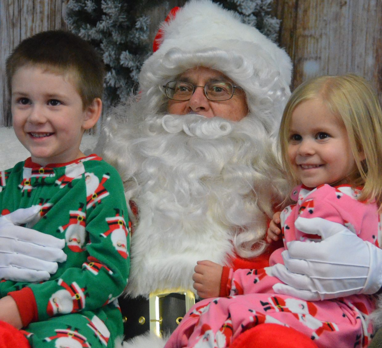 Siblings Rylan, 4, and Xia Hedman, 3, smile for the camera in their holiday pajamas along with jolly old St. Nick during Letters to Santa Tuesday at Justin Stokes State Farm Insurance.