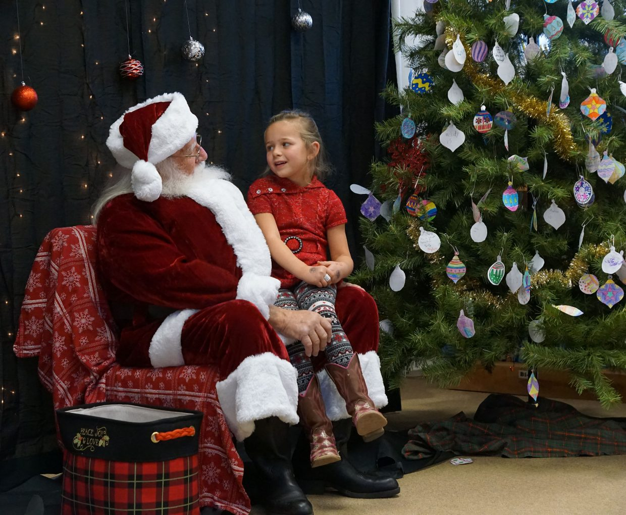 Macie Pearcey takes a turn to talk with Santa Claus.