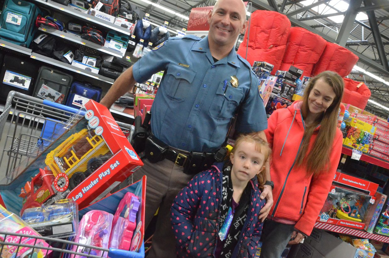 From left, Colorado State Patrol's Andy Bogue, Emelia Stilson and Ashley Piep take a break from Saturday morning's Shop with a Cop at Walmart. 6-year-old Emelia selected items both for herself and for her 3-year-old brother.