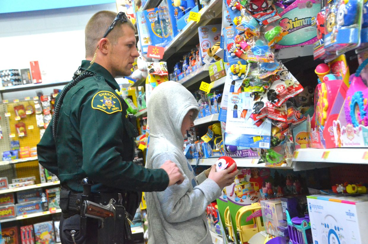 Ryan Hampton, left, and Cedar Higley inspect an array of toys during Saturday morning's Shop with a Cop at Walmart.