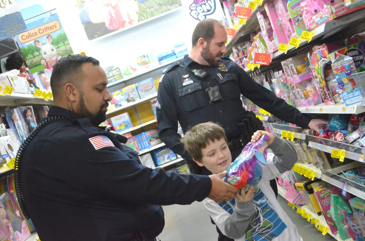 Taden Jones shows one of his toy selections to Craig Police Department officers Junior Gonzales, left, and Will Roland during Saturday morning's Shop with a Cop at Walmart.