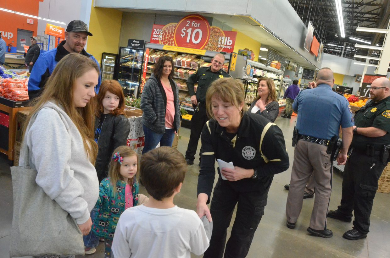 Moffat County Undersheriff Charlene Abdella greets kids to begin Saturday morning's Shop with a Cop at Walmart.