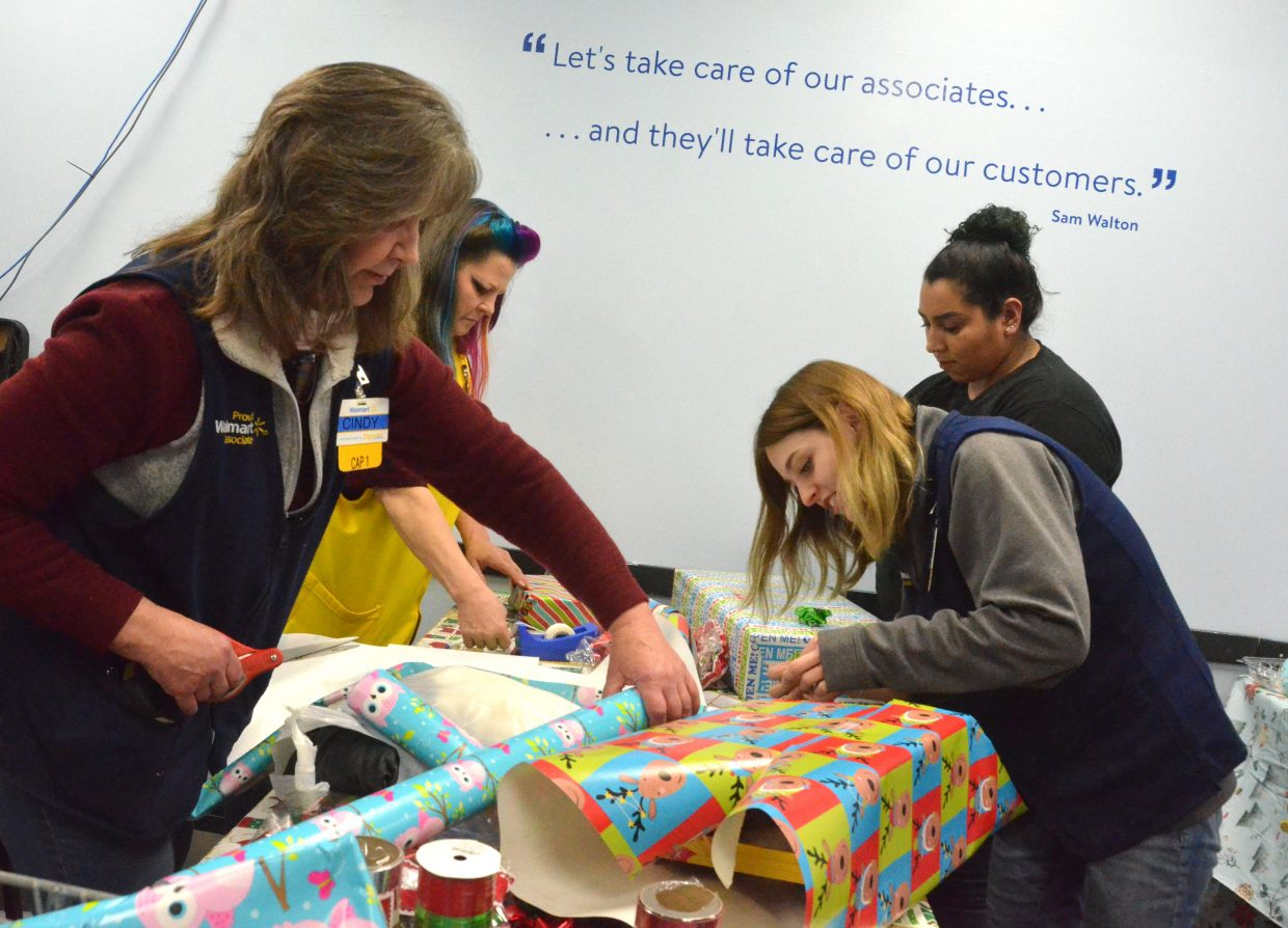 Walmart employees work the gift-wrap station during Saturday morning's Shop with a Cop at Walmart.