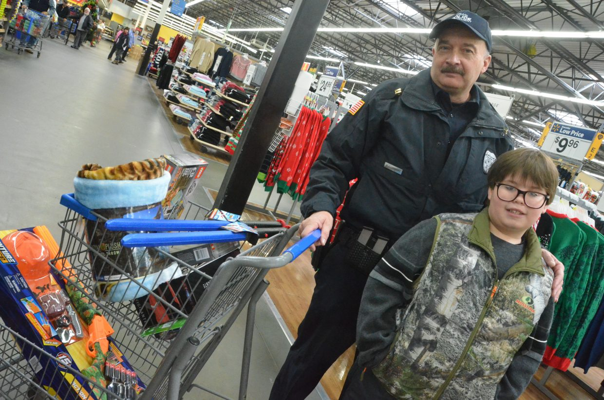 Tim Adams, right, and Bill Leonard move into the checkout line during Saturday morning's Shop with a Cop at Walmart.