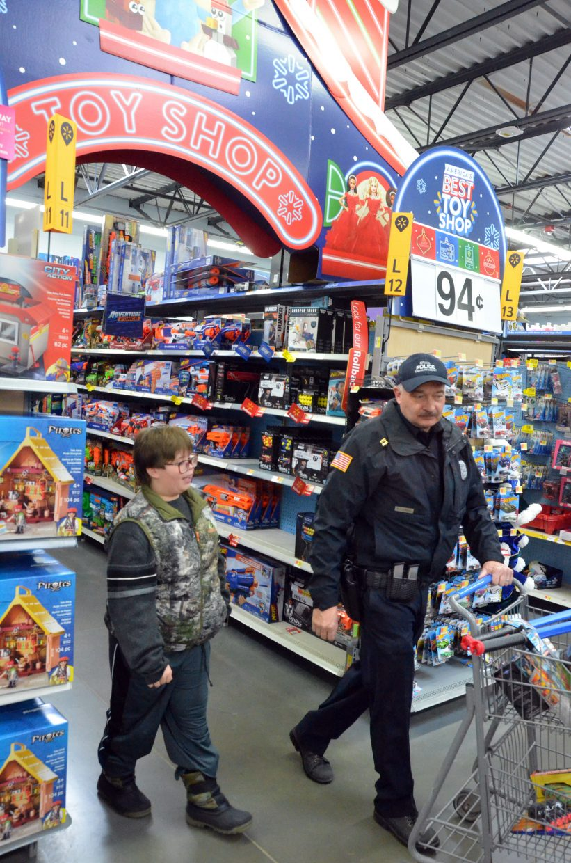 Tim Adams, left, and Bill Leonard head out of the toy department during Saturday morning's Shop with a Cop at Walmart.