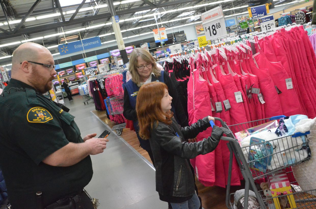 Makaylee Hogan makes a turn in the apparel department during Saturday morning's Shop with a Cop at Walmart.