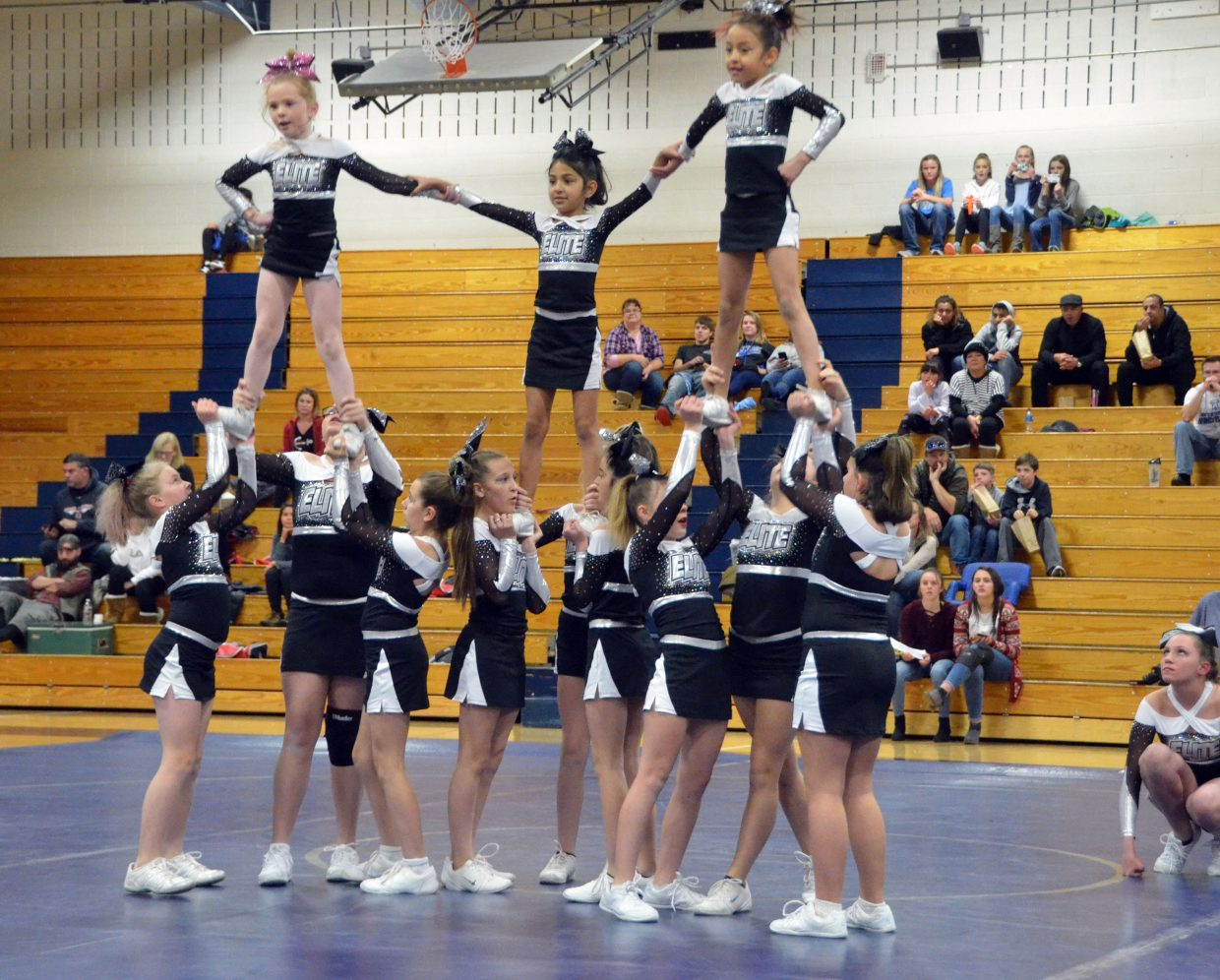 The Moffat County Elite Cheer team poses during their routine between rounds of a Tuesday night triangular wrestling meet.