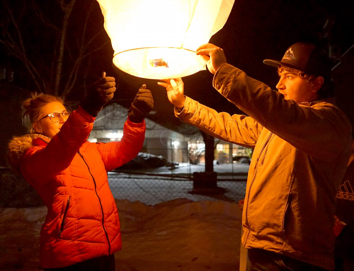 Bryanna McFadden and Austin Gabbert prepare to release a paper lantern in honor of Gabbert's grandfather Robert Lee Gabbert and his Aunt Wilma Alberts who both died earlier in the year.