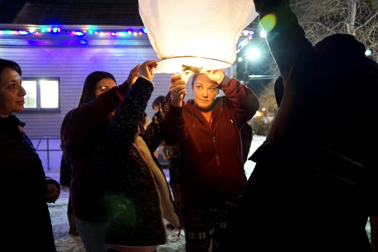 A small group gathers to hold a lantern until it fills with enough hot air to fly into the icy sky.