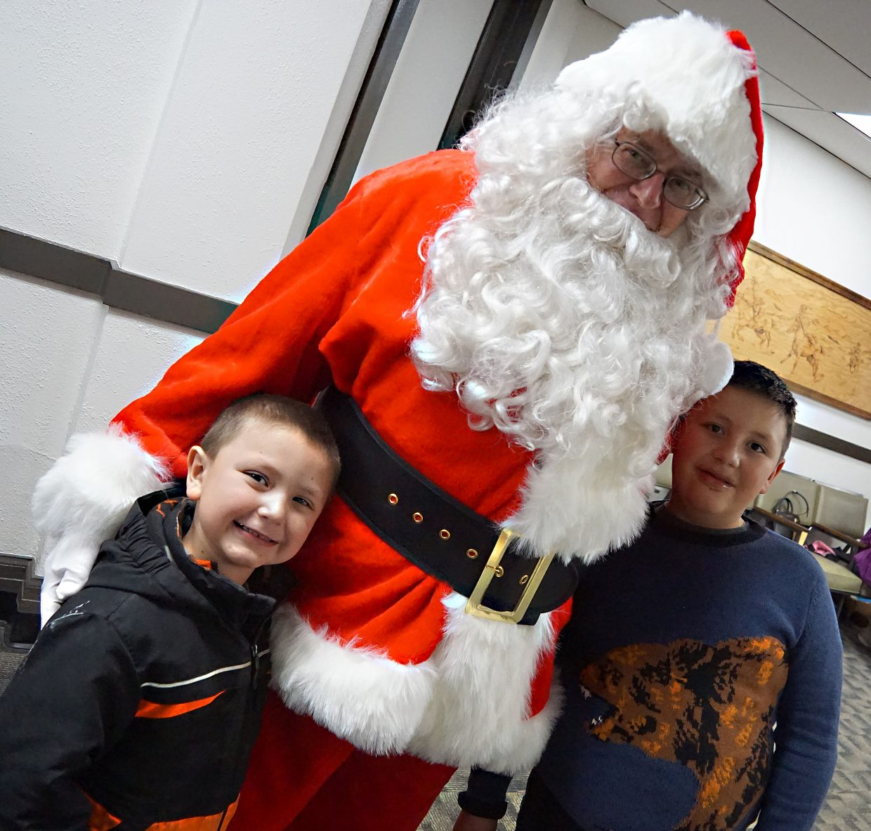 Zachariah Vesely, 6, and Ryan Vesely, 9, sandwich Santa with a Christmas-sized hug.