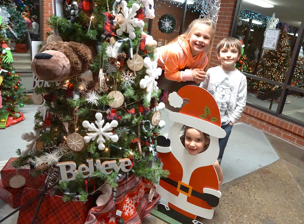 Three of your designers — Kylee Jo Hammer, top left, Grayden Jones, right and Avery Jones as Santa — smile next to the tree they decorated based on the book
