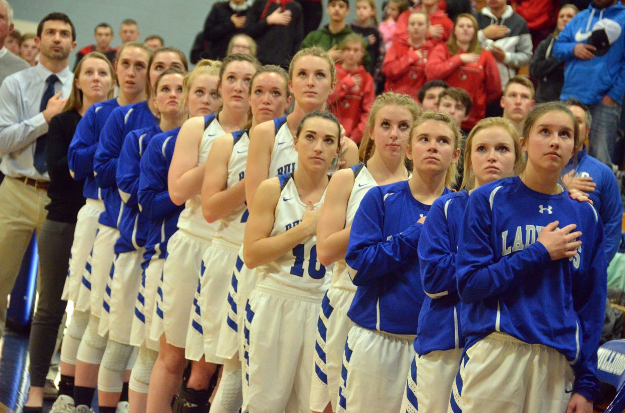 The Moffat County High School girls varsity basketball team observes the national anthem.