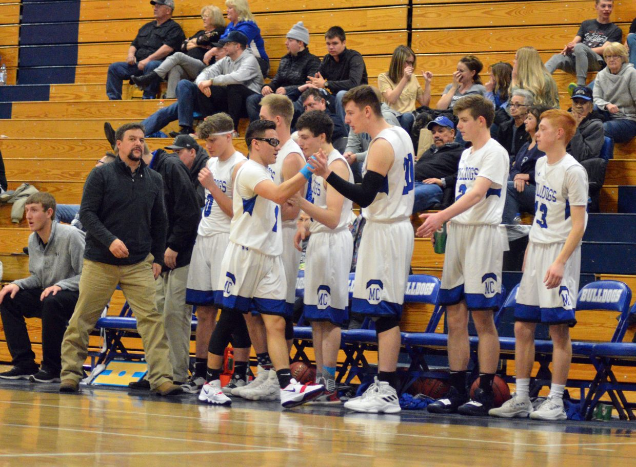 Moffat County High School's Victor Silva exchanges high-fives with teammates as he comes off the court.