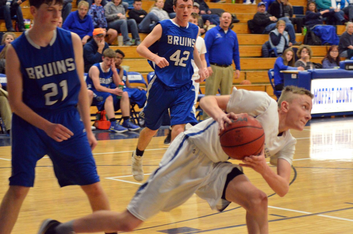 Moffat County High School's Logan Hafey scoops up the ball during boys JV basketball