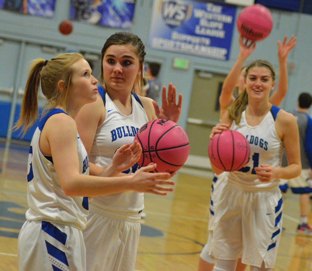 From left, Moffat County High School's Reese Weber, Jenna Timmer and Rylie Felten get warmed up for the second half.