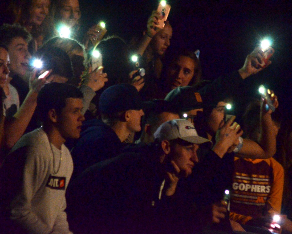 The Moffat County High School student section provides extra lighting via cell phone during pre-game introductions.