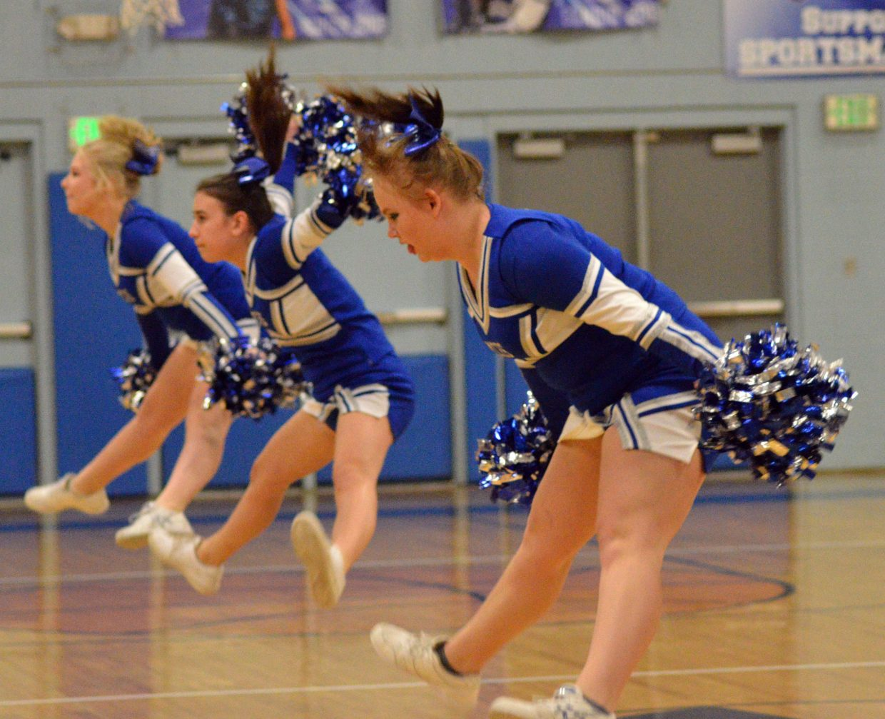 Moffat County High School cheerleaders do a coordinated leap.