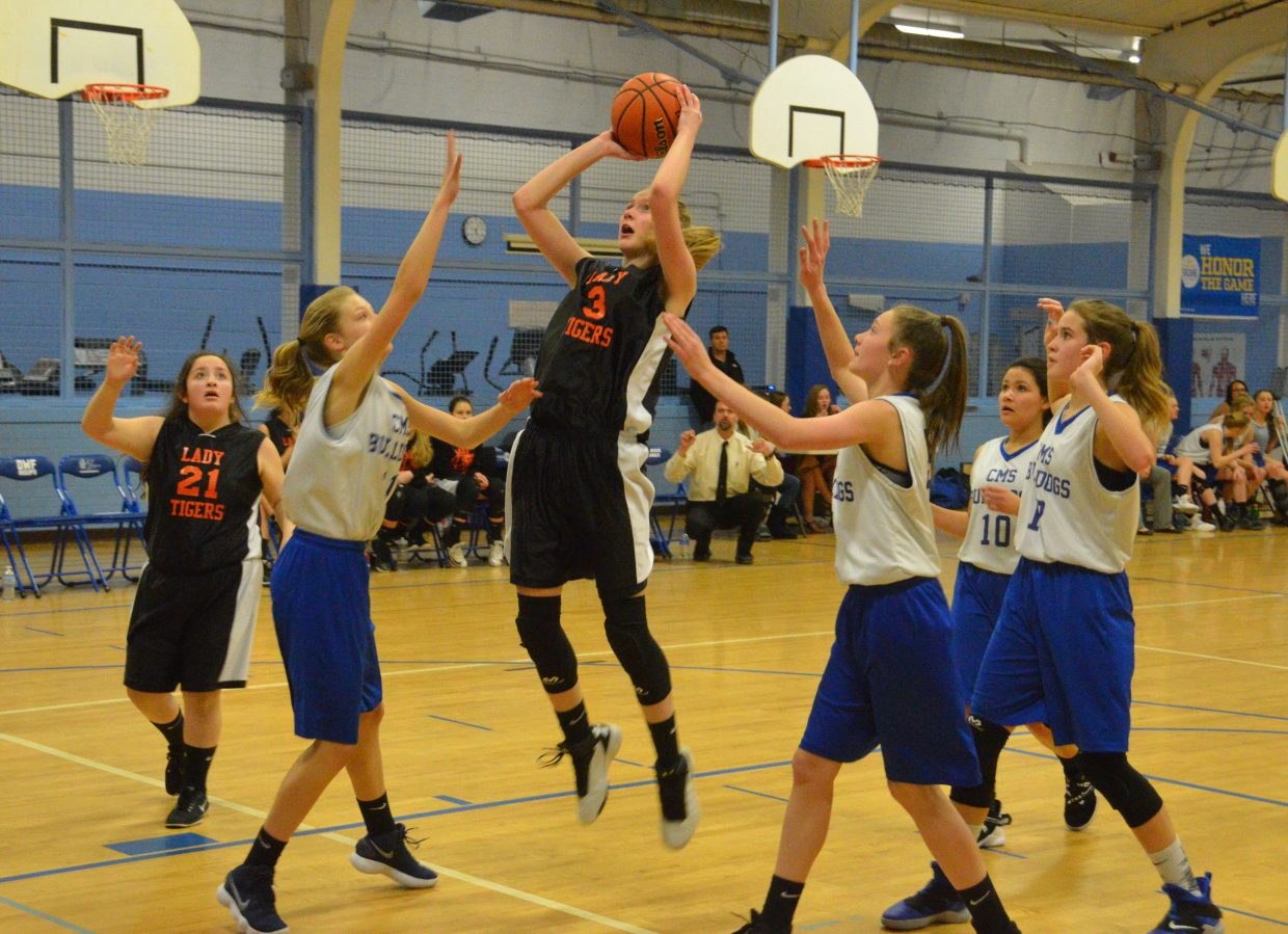 Craig Middle School basketball players converge as Hayden's Emma Seagrave takes a jump shot.