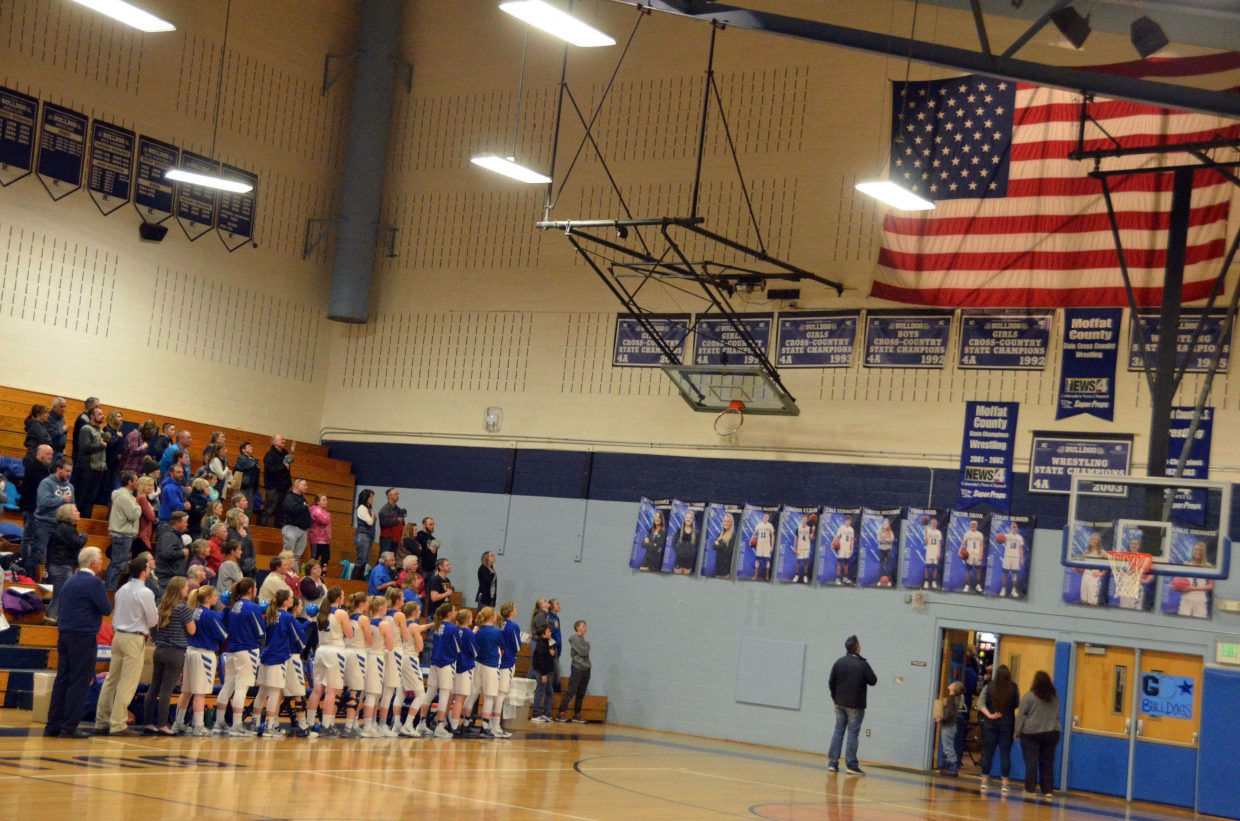 The Moffat County High School girls basketball team and crowd observe the national anthem.