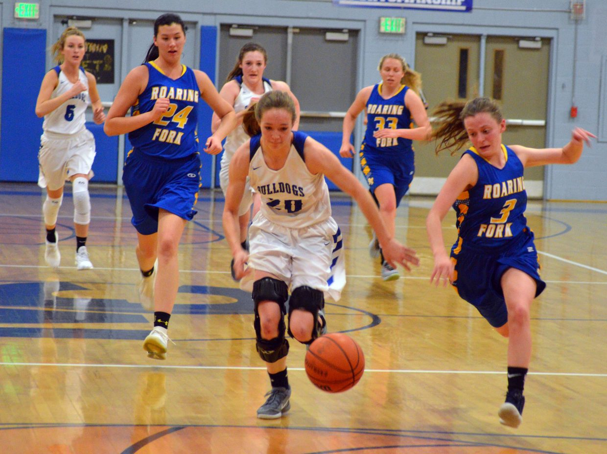 Moffat County High School's Madie Weber knocks away the ball from Roaring Fork and chases after it.