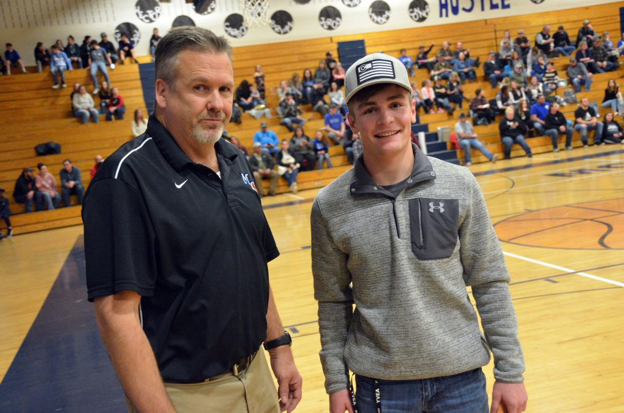 Moffat County High School Athletic Director Bobby Howard leads Daylon Frentress to collect his prize after winning a drawing Saturday. Frentress won a prize package worth $1,000  at Olde Town Hot Springs.