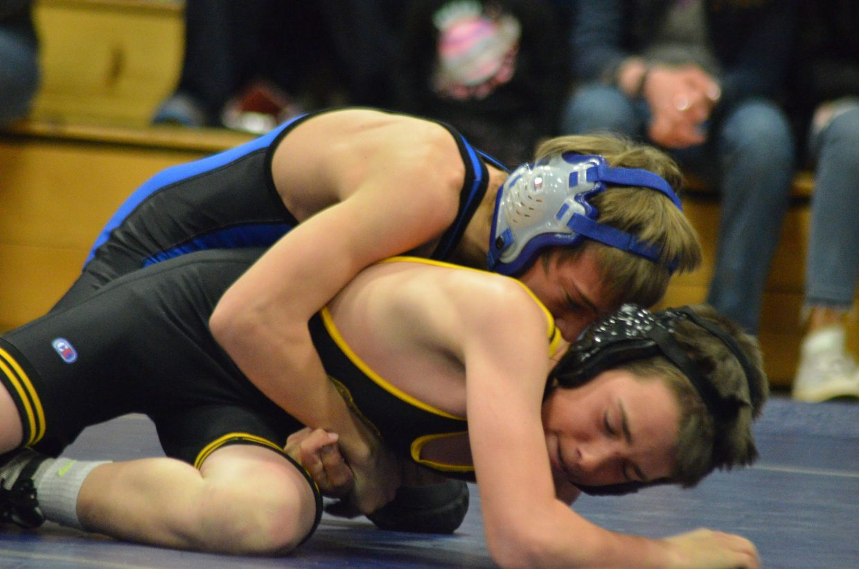 Craig Middle School's Brody Wiser drives Meeker's Jake Blazon to the mat.