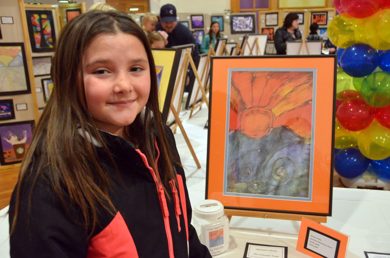 Sandrock Elementary School fourth-grader Felicity Forbes shows off her pastel drawing during the opening night of Cherish the Little Things Art Show.