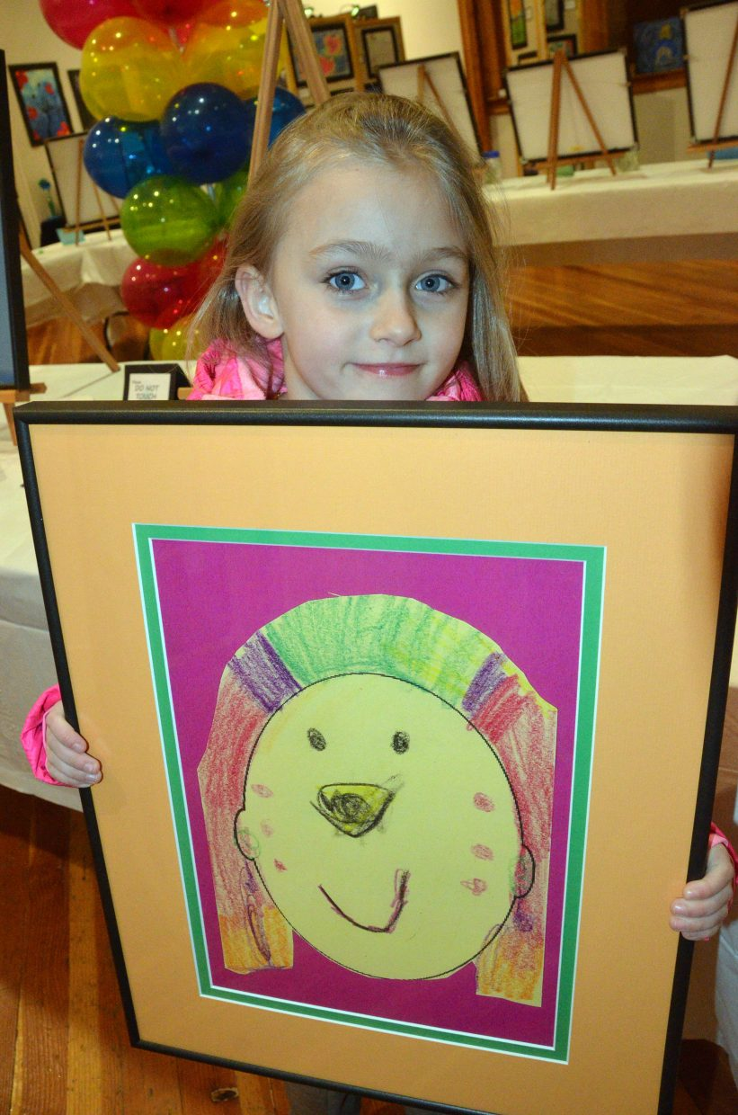 Sandrock Elementary School kindergartner Lillian Gregory holds up her artwork during the opening night of Cherish the Little Things Art Show.