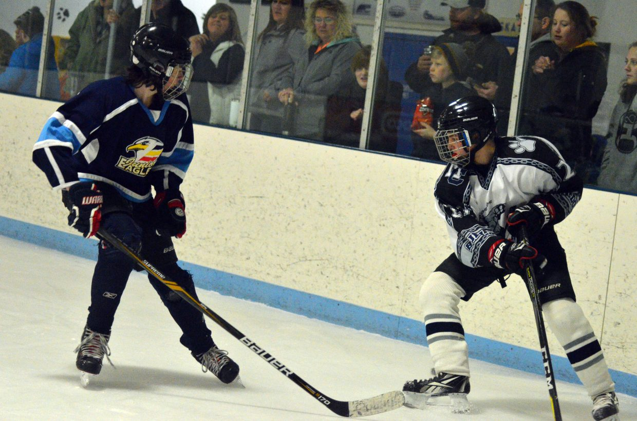 Moffat County Bulldogs' Clay Durham looks to get the puck out of the corner.