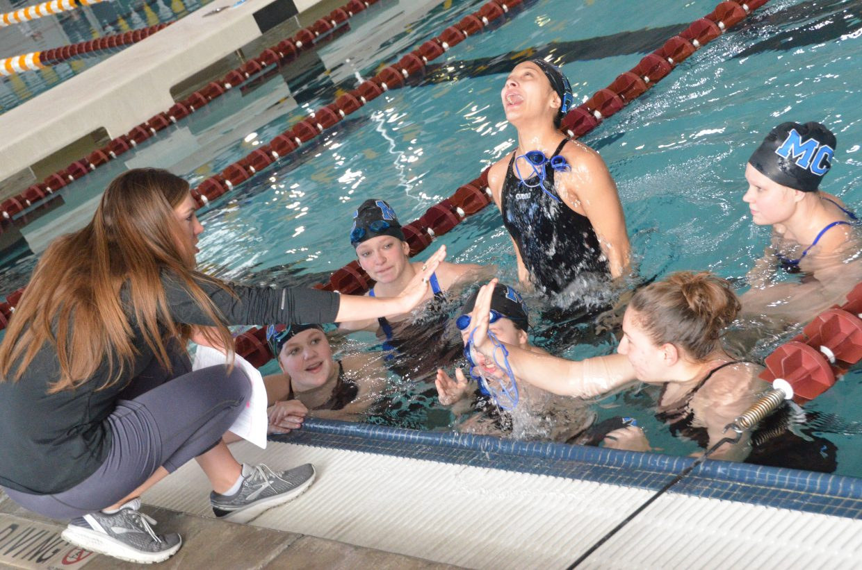 Moffat County High School coach Meghan Francone exchanges high-fives with swimmers in the warmup pool at the Southwest Conference Championships.