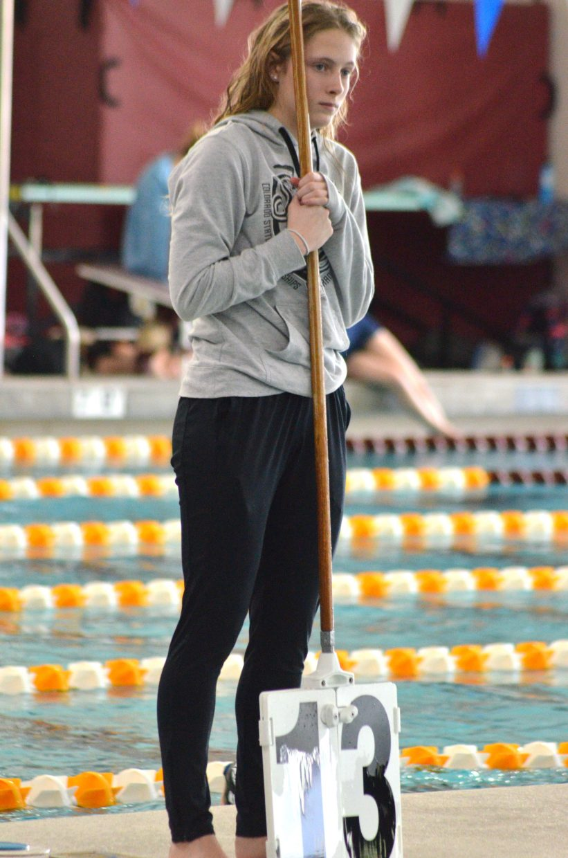 Moffat County High School's Kelsey McDiffett holds the sign for lap count during teammate Alexa Neton's competition in the 500 freestyle at the Southwest Conference Championships.